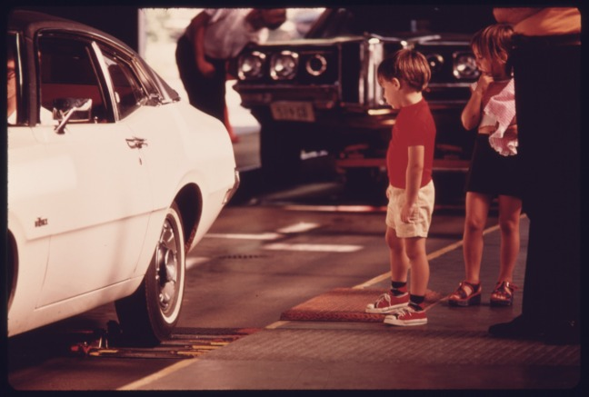 child looking at car