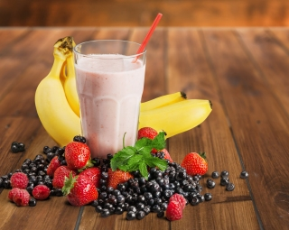 Banana and strawberry smoothie in glass on white background